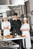 Team Of Confident Chefs In industriellt kök Arkivbild