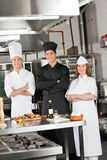 Team Of Confident Chefs In industriellt kök Arkivbild