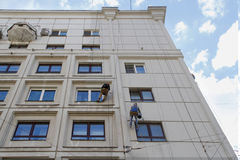 Team of construction climbing workers reconstructing the facade of building in Moscow Royalty Free Stock Images