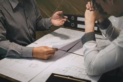 Team of construction engineering or architect partner discuss a blueprint while checking information on drawing and sketching royalty free stock photos