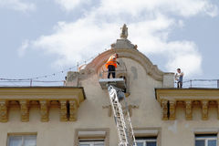 Team of construction workers are reconstructing the facade of building in Moscow Royalty Free Stock Image