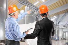 Team of construction workers at work place i. A team of construction workers with orange helmets at work place in a factory royalty free stock photography