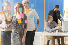Team of coworkers. Going through colorful sticky notes on a glassboard Royalty Free Stock Photography