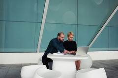 Team of creative designers working together on net-book while sitting in office interior Stock Photos