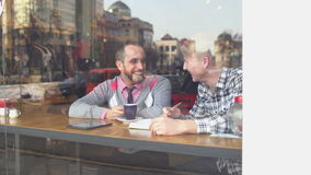 Team Of Creative People. Meeting In A Cafe. Attractive two young businessmen are discussing a project. Two Young Man in Coffee Shop. Men are sitting in front of stock video footage
