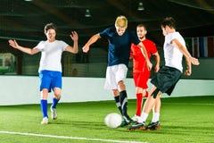 Team, das den Fußball oder Fußball Innen spielt Stockbilder