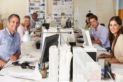 Team, das an den Schreibtischen im besetzten Büro arbeitet Lizenzfreies Stockfoto