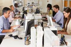 Team, das an den Schreibtischen im besetzten Büro arbeitet Stockbild