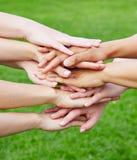 Team, das Hände für Motivation in der Natur stapelt Stockbild