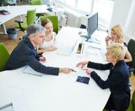 Team, das am Schreibtisch im Geschäftstreffen sich bespricht Lizenzfreie Stockfotos