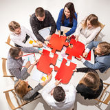 Team das Sitzen hinter Schreibtisch und überprüfen die Berichte und sprechen Beschneidungspfad eingeschlossen Stockfoto