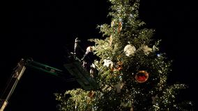 Team decorating Christmas tree at market decoration in Strasbourg. STRASBOURG; FRANCE - CIRCA 2018: Workers working on the top of telescopic crane in central stock footage