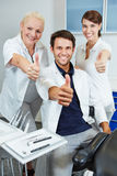 Team at dentist holding thumbs up Royalty Free Stock Photos