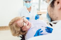 Team of dentists talking to senior patient in their surgery Royalty Free Stock Image