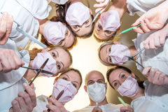 A team of dentists. With tools and masks bending over patient Stock Images
