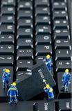 Team der Bauarbeiter, die an einer Tastatur arbeiten Lizenzfreie Stockfotos