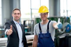 Team in der Fabrik mit den Daumen oben Stockfotos