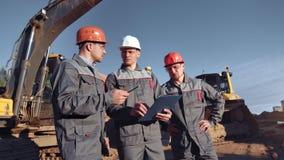Team der professionellen m?nnlichen Technikarbeitskraft in der Uniform Arbeitsplan an der Baustelle besprechend stock video