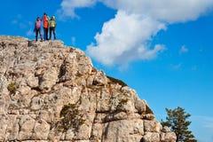 Team der Wanderer auf dem felsigen Gipfel Stockfotografie