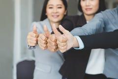 Team des Geschäfts Zusammenschluss, Daumen als Si bearbeitend und zeigend stockbild