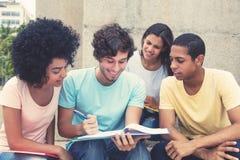 Team des Lachens von den internationalen Studenten, die zusammen lernen stockfotos