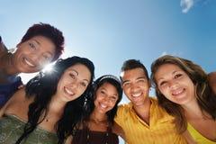 Team des Mannes und der Frauen, die, lächelnd an der Kamera umfassen Stockfoto