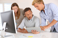 Team of designers checking news on tablet Stock Image