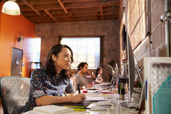 Team Of Designers Working At Desks In Modern Office Royalty Free Stock Photography