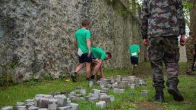 Team die stenen opnemen en hen dragen stock videobeelden