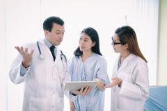 Team die van arts een vrouwelijke patiënt onderzoeken stock afbeeldingen