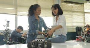 Team die van elektronikaingenieur, aan een project samenwerken om robot te bouwen samenwerken stock videobeelden