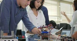 Team die van elektronikaingenieur, aan een project samenwerken om robot te bouwen samenwerken stock footage
