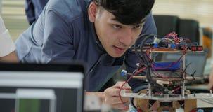 Team die van elektronikaingenieur, aan een project samenwerken om robot te bouwen samenwerken stock video