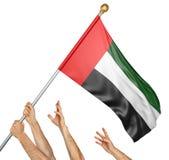 Team die van volkerenhanden de Verenigde Arabische nationale vlag van Emiraten opheffen Stock Afbeelding