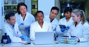 Team die van wetenschapper over laptop 4k bespreken stock footage
