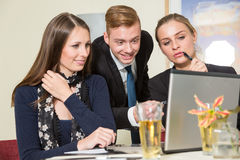 Team discussing and brainstorming together at computer Royalty Free Stock Image