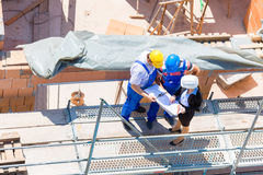 Team discussing construction or building site plans royalty free stock image