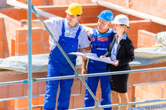 Team discussing construction or building site plans Royalty Free Stock Photo