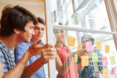 Team discussing ideas on sticky notes Stock Image