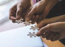 Team disponendo un puzzle di quattro puzzle per il concetto del gruppo fotografie stock