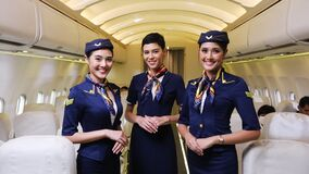 Team of diverse flight attendant posing with smile at middle of the aisle inside aircraft with passengers seated on the background