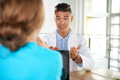 Team of doctor and nurse discussing a patient diagnosis sitting at the desk in bright modern office Royalty Free Stock Photos