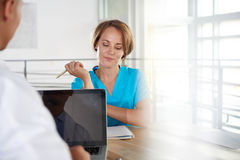 Team of doctor and nurse discussing a patient diagnosis sitting at the desk in bright modern office Royalty Free Stock Images