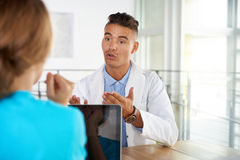 Team of doctor and nurse discussing a patient diagnosis sitting at the desk in bright modern office Stock Images