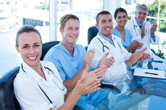 Team of doctors applauding. In the meeting room stock photo