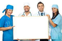 Team of doctors with blank banner. Happy team of four doctors holding a blank billboard and a doctor woman pointing to copy space of banner isolated on white Stock Image