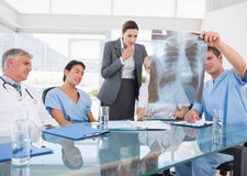 Team of doctors and businesswoman examining xray Stock Images