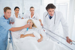 Team of doctors carrying patient on stretcher Stock Image