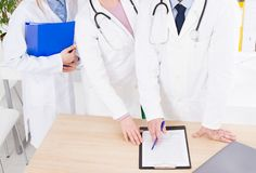 Team of doctors in clinic. people in white coats. Medical insurance. Copy space. Team of doctors in clinic. people in white coats. Medical insurance. Copy space royalty free stock image