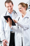 Team of doctors in clinic with tablet computer Stock Images